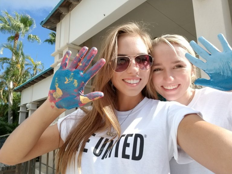 Two volunteer girls pose with paint on their hands