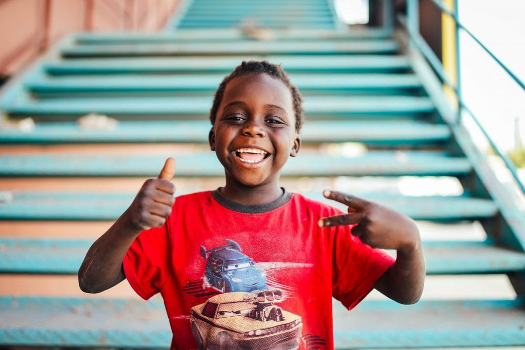 boy with thumbs up in front of stairs